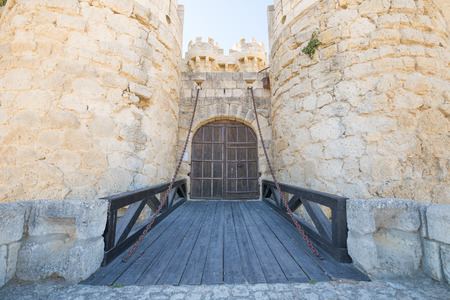 ancient footbridge access and wooden door of fifteenth century landmark and monument, castle in Ampudia village, Palencia, Castile Leon, Spain, Europe
