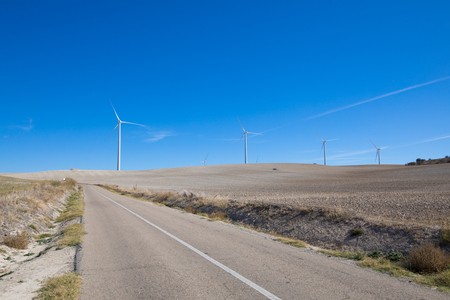 rural road next to wind power turbines on winter meadow near to Ampudia town, in Palencia Spain Stock Photo
