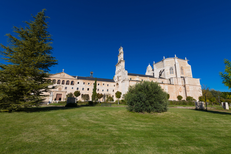 side view of Monastery Santa Maria de la Vid, with church, landmark and monument from twelfth century, with green grass and blue sky, in Burgos, Castile and Leon, Spain, Europe