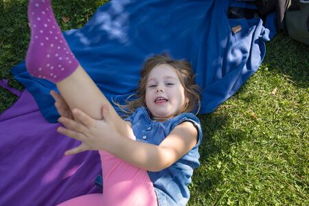four years old blonde girl lying on towels in the green grass of park with hand in leg looking and smiling