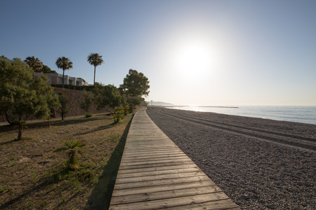 landscape at dawn of wooden walkway in Els Terrers Beach, in Benicassim, Castellon, Valencia, Spain, Europe. Palm trees, buildings, blue clear sky and Mediterranean Sea