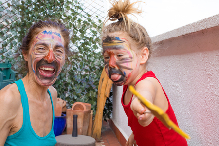 portrait of happy family with painted faces in party at terrace of house, three years old child sticking out tongue next to woman laughing