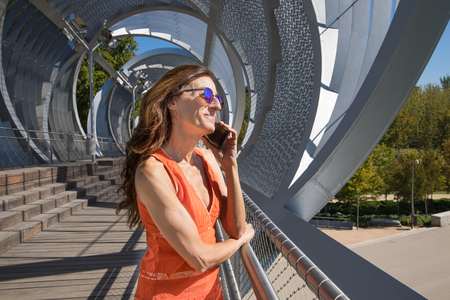 woman with orange shirt in summer, at modern urban footbridge, talking on mobile, in Madrid city, Spain, Europe