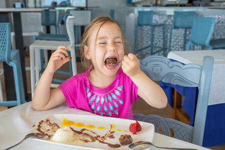 funny cute four years old blonde girl opening big mouth to eat with spoon a delicious sweet dessert: black chocolate, vanilla ice cream, strawberries and mango sauce, sitting in restaurant