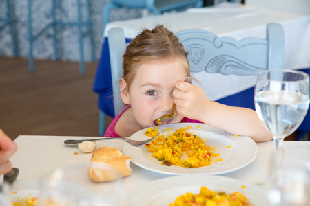 four years old blonde girl eating Spanish paella rice with spoon from white plate, sitting in restaurant. Funny portrait looking at camera 版權商用圖片
