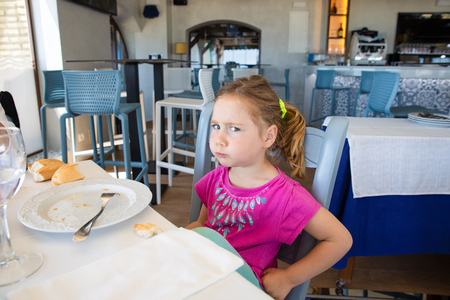 side of four years old blonde little girl with pink eating bread, looking at with angry expression face, sitting indoor in restaurant Banque d'images