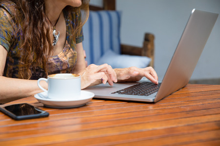 detail of woman hands typing on keyboard of pc laptop computer, with coffee cup and black mobile smart phone blank screen on brown wooden table