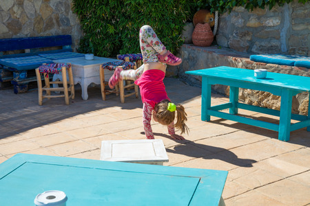 four years old blonde girl trying to do the somersault or handstand on floor of a roof with tables