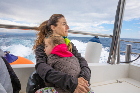 mother hugging her daughter, four years old blonde girl with pigtail, sitting on the stern of motorboat sailing from Tarifa (Cadiz, Andalusia, Spain) in Strait of Gibraltar