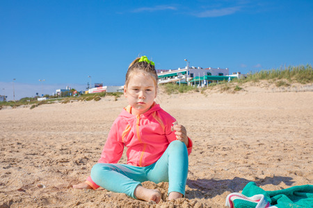 cute four years old blonde girl with pigtail, pink jacket and green leggings, sitting on the sand looking at with challenging expression face, on beach named Palmar, in Vejer, Cadiz, Spain