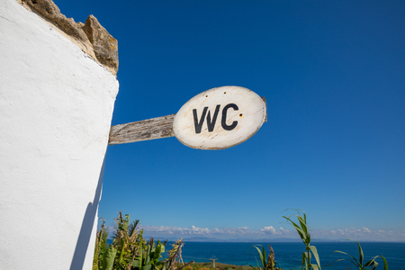 wood signpost with text WC (Water Closet), toilet, in Cadiz, Andalusia, Spain, and on the horizon the ocean and Africa coast Imagens