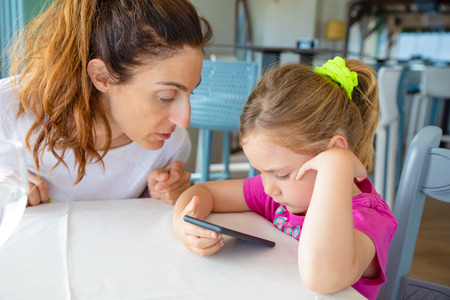mother and her daughter, four years old blonde caucasian girl, sitting in a restaurant in summer, watching internet together on smartphone or mobile phone