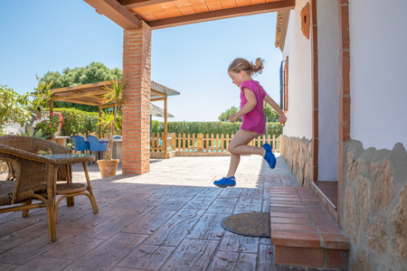 side view of four years old blonde girl with pink shirt jumping, or taking a great leap, from the exterior doorway to the porch of the house