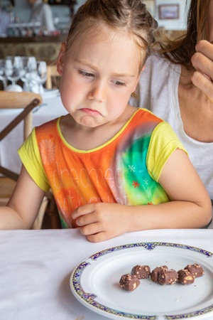 little girl looking with displeased expression at chocolates on her plate, sitting on mother legs, in restaurant