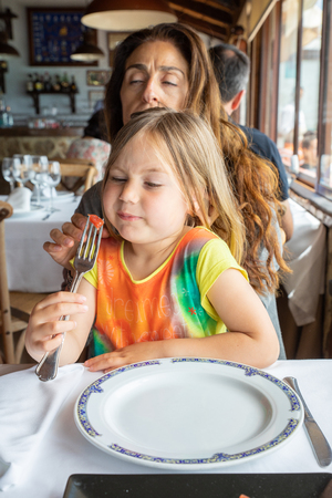 funny scene: four years old blonde little girl looking with disgust at a piece of quince on a fork sitting on mother legs in restaurant
