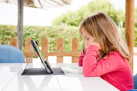 Four years old blonde girl with red shirt sitting, resting head in hands, watching mobile phone and digital tablet on the table