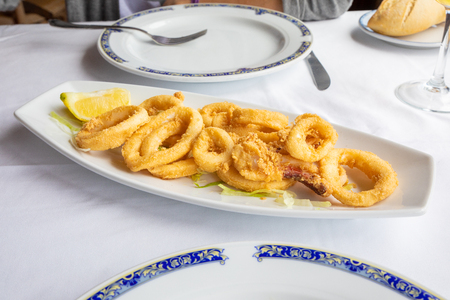 white tray with rings of squid, breaded and fried, with lemon and lettuce, typical food of Andalusia (Spain, Europe) on white tablecloth of restaurant ready to eat