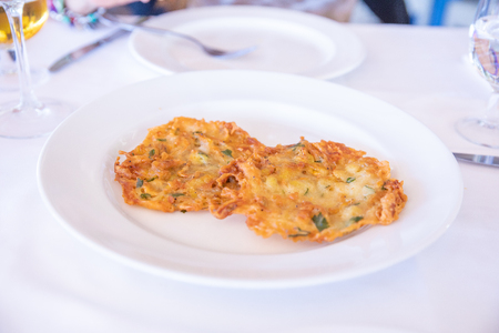 two little shrimp omelette fried with parsley, typical Andalusian food and Spanish tapas, in dish on white tablecloth of restaurant in Spain