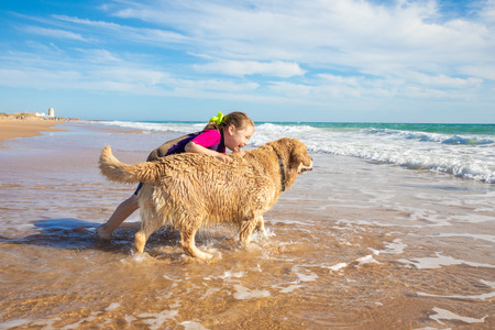 smiling four years old little girl talking and playing with a dog, golden retriever breed pedigree, on seashore in Palmar Beach (Vejer, Cadiz, Andalusia, Spain) Stock Photo