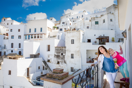 funny scene: mother and happy little girl in balcony and cityscape of Vejer old town, beautiful and typical white buildings in Cadiz (Andalusia, Spain, Europe) 写真素材