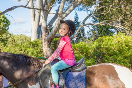 cute little girl four years old with pink shirt and black cap, looking smiling, riding catching the reins of the horse in a forest