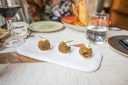 three squid croquettes with alioli, typical Mediterranean sauce of Spain, and chive on white tray over table at restaurant Фото со стока