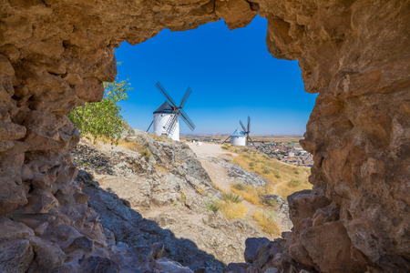 two classic wind mills through a hole in wall in Consuegra town (Toledo, Castilla La Mancha, Spain). Built from the Sixteenth to the Nineteenth century. Typical from Quixote land and his book Stockfoto