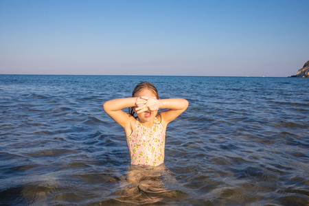 little girl with swimsuit in the water of Mediterranean sea covering her eyes with hands to protect herself from the sun, in Cabo de Gata Natural Park (Almeria, Andalusia, Spain)