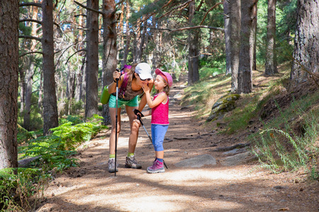 mountaineer little child laughing and talking to woman, with caps and trekking sticks, on a footpath in a forest of Canencia (Madrid, Spain, Europe)