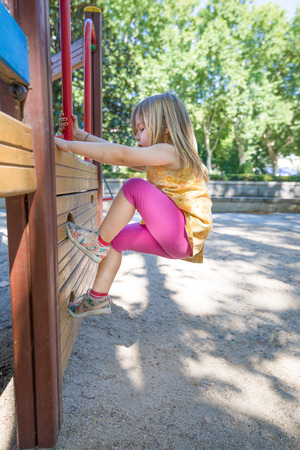 Three years old blonde girl with yellow dress and pink tights playing to climb on wooden construction in outdoor playground, in public park of Madrid