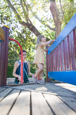 Three years old blonde girl with yellow dress playing on wooden construction in outdoor playground, with mother woman, in public park of Madrid