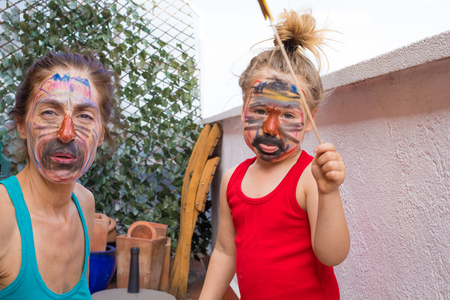 portrait of happy family with painted faces, three years old child sticking out tongue next to woman, in terrace of house