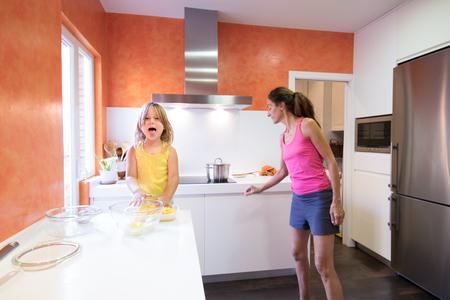 Niño feliz rubia de cuatro años preparando patatas crudas para cocinar en la cocina, mirando y sacando la lengua sonriendo, junto a la madre de la mujer