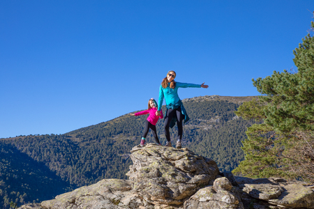 mountaineer happy family (woman and five years old girl) posing on the top of rock in mountain of Fuenfria Valley, in Guadarrama Natural Park (Cercedilla, Madrid, Spain) Imagens
