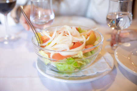 mixed salad with green lettuce, sliced tomatoes and onion, in glass bowl on white tablecloth in table of restaurant, with cutlery to serve, ready to eat