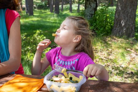 funny little daughter, four years old blonde girl making faces playing with food, eating pasta from a plastic lunch box next to her mother in a table picnic in countryside 写真素材