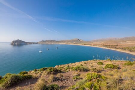 bay of Genoveses and sandy long beach, with yachts and sailboats anchored, from mountain, in Gata Cape Natural Park, in Almeria (Nijar, Andalusia, Spain, Europe)