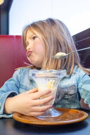 Funny portrait of five years old blonde little child with blue denim jacket, sitting in red sofa and black table in a restaurant, making faces eating vanilla ice cream with spoon from crystal cup