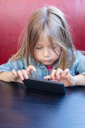 Portrait of five years old child with blue denim jacket, sitting in red sofa and black table in a restaurant, touching with finger a smartphone mobile in her hands. vertical shot