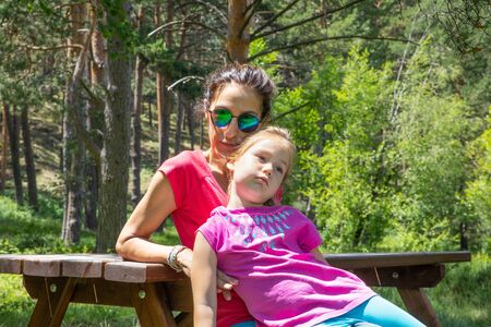 funny scene: boring little daughter, four years old girl, resting sitting on her mother legs on a picnic bench in a forest of the country