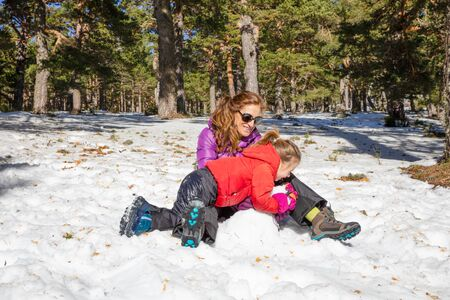 Happy family (woman and daughter, five years old blonde girl), playing on the snow in a forest in mountain Фото со стока