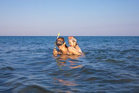 funny scene with woman and little girl piggybacking, with diving glasses to snorkeling, in the water of a beach in Andalusia, both laughing 스톡 콘텐츠