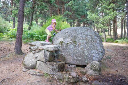 five years old blonde girl walking on rocks and above a fountain, on summer, in a forest in Guadarrama Natural Park (Madrid, Spain, Europe) Фото со стока