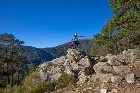 happy family (woman and five years old girl) posing on the top of rock in mountain of Fuenfria Valley, in Guadarrama Natural Park (Cercedilla, Madrid, Spain) Фото со стока
