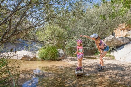 adventurous family: woman pointing nature to her daughter, five years old girl, with caps, discovering a river of Camorza Gorge (Madrid, Spain, Europe) Фото со стока