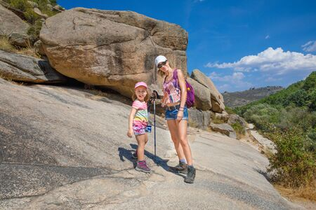 adventurous family girl power: mother and daughter, five years old girl, with caps and trekking sticks, posing in rocky mountain of Camorza Gorge (Madrid, Spain, Europe) Фото со стока