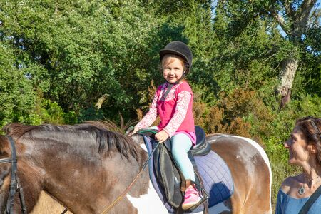 cute little girl four years old with pink shirt and black cap, looking smiling, riding a horse in a forest next to her mother Stockfoto