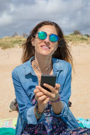 portrait of brunette woman with sunglasses and blue clothes smiling and looking at with mobile phone smartphone in her hands, sitting on towel on the beach Фото со стока