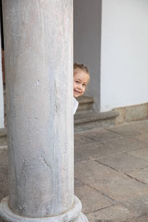 little child four years old peeking face and looking at smiling behind ancient marble column
