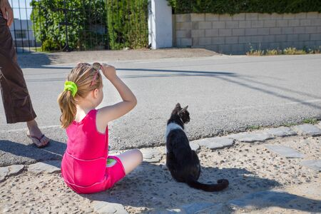 little girl, five years old child holding sunglasses, sitting on the ground next to white and black cat, together looking at the street in Summertime Фото со стока